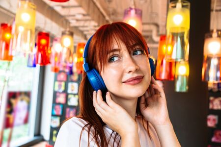 Happy girl listens to music on headphones in cafe
