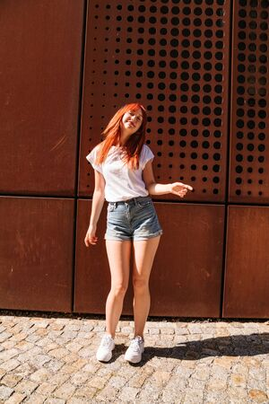 Young woman moves in dance on sunny street alone