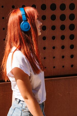 Smiling young girl listening to music on street pressing headphones to her head