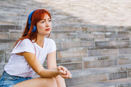 Young beautiful girl sits on stairs in city wear
