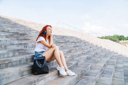 Young girl enjoys sun and music sitting on stairs