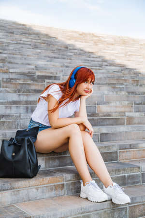 Girl listens to music sitting on stairs in shade