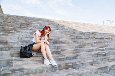 Young girl in headphones on stairs. Urban fashion 免版税图像 - 150641517