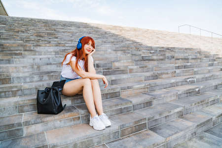 Young girl in headphones on stairs. Urban fashion