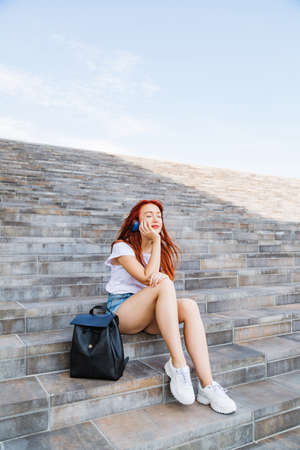 Young girl enjoys sun and music sitting on stairs 免版税图像 - 150641522