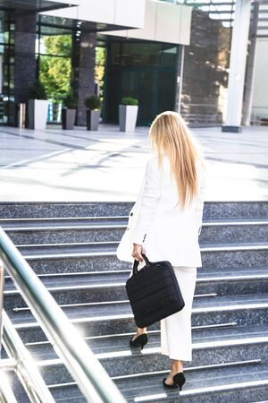 Young business woman in white suit outside Foto de archivo
