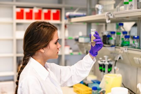 Female scientist holding flask with medicine in laboratory Banque d'images