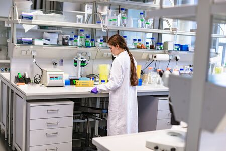 Girl scientist studying notes near lab equipment