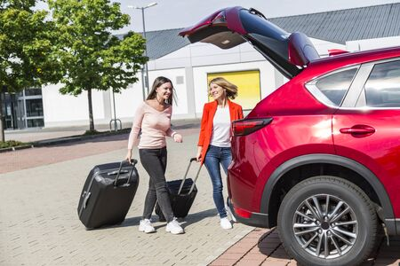 Girls approach cars open trunk with big suitcases Stock fotó