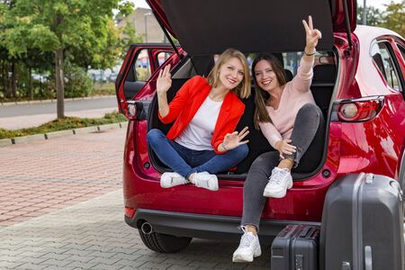 Two girls in trunk of red car posing for camera Foto de archivo