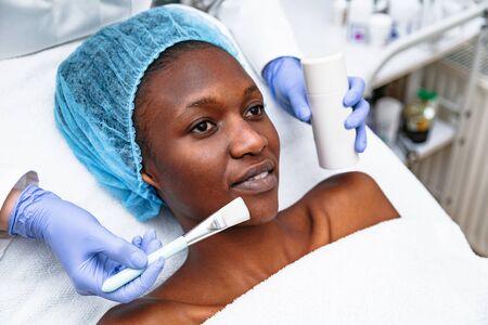 Female hands make woman facial mask in beauty salon