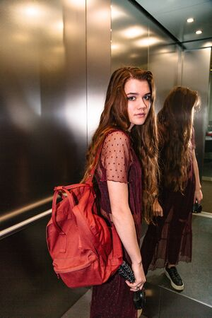 Woman stands in moving elevator turning around
