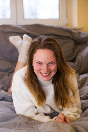 Young woman in knitted sweater and bikini in bed
