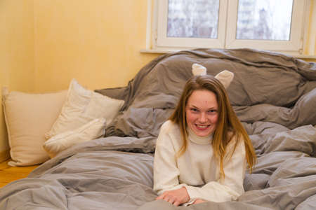 Smiling girl in warm sweater and socks lies on bed