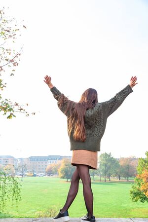 Young girl in autumn park spread arms to sides