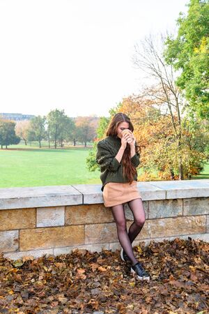 Girl sits on fence drinking coffee from paper cup