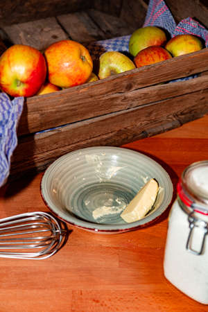 Kitchen utensils, wooden box of ripe apples, saucepan, sugar in jar and butter