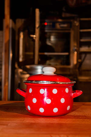 Red saucepan with speckled print on table in the kitchen 免版税图像