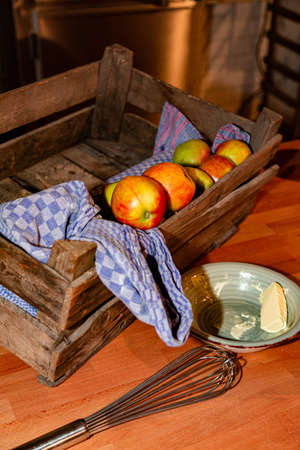 Kitchen utensils, wooden box of ripe apples, saucepan and butter
