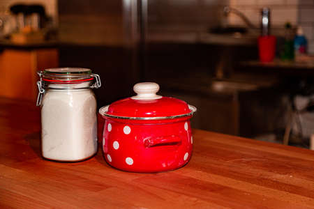 Red saucepan with speckled print with sugar jar on table in the kitchen