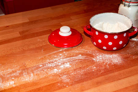 Red saucepan with white flour and sugar jar on table in the kitchen 免版税图像