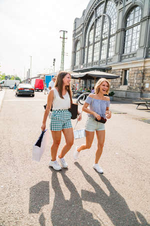 Two young girls after shopping in sunny weather