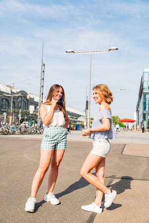 Two sexy smiling girls in summer clothes in city