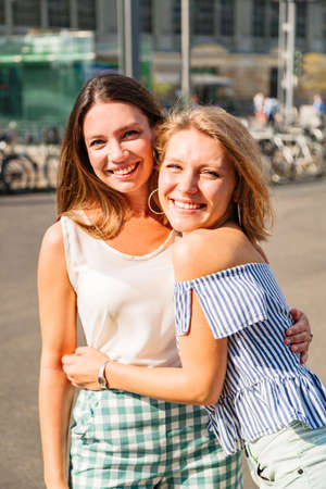 Blonde girl hugs her friend and smiles at camera 免版税图像