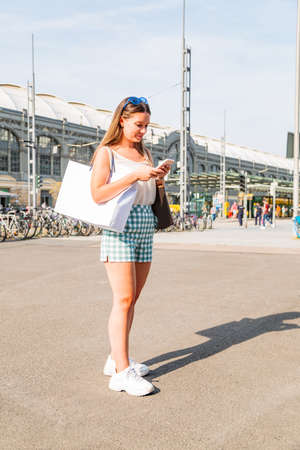 Woman walking in street and using her smart phone