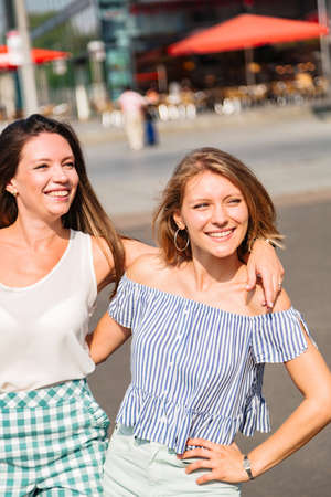 Two young girls friends walk in city in summer day