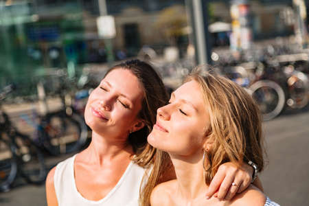 Close up portrait of two young women in city