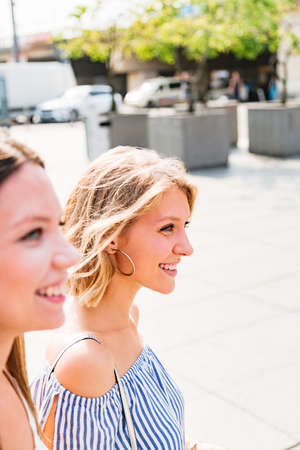 Two smiling girls in summer clothes in city