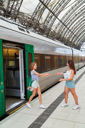 Happy meeting of two girlfriends in train station