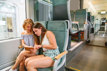 Two young women sitting in modern train and discussing something