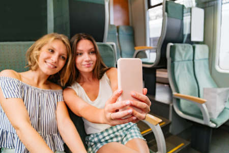 Young women taking pictures of themselves in train