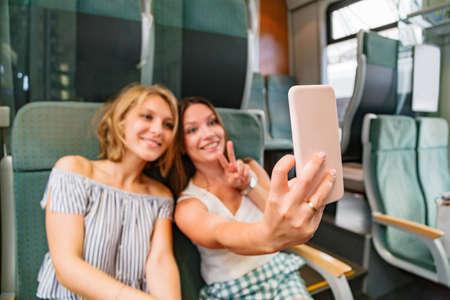 Two women taking selfie in train showing peace sign