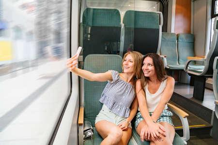 Two smiling girlfriends in train taking selfies