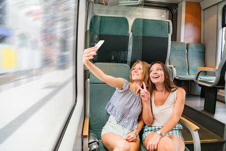 Two smiling girlfriends in train taking joint selfie