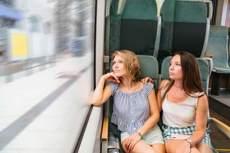 Women in summer clothes sitting in train by the window