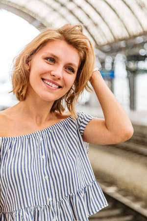 Woman straightens her hair and standing on a train platform