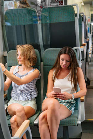 Two young girlfriends using smart phone in a train