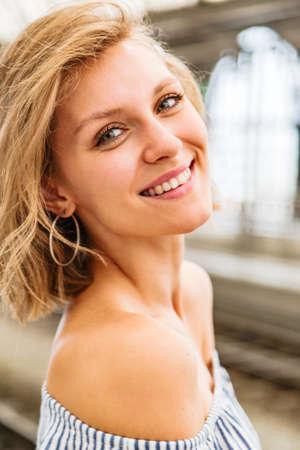 Portrait of smiling blonde woman standing in half-turn