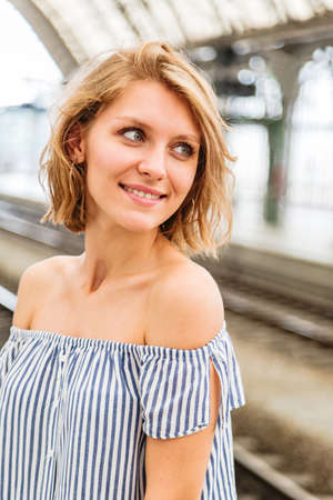 Blonde woman waiting for a train at railway station