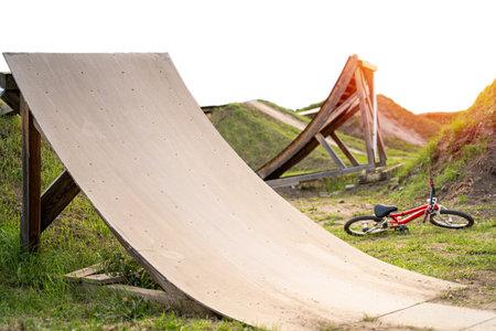 Bike ramp made of wood near laying red bike on sunset
