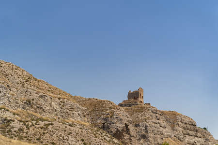 View of outer wall of stone old tower of fortress in spanish desert