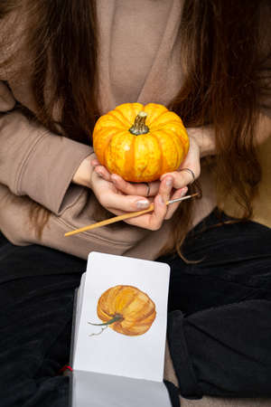 Young brunette long-haired woman in knitted warm cozy sweater sitting holding small orange pumpkin near watercolor pumpkin drawing on autumn weekend day. Hobby, arts, education and leisure activity