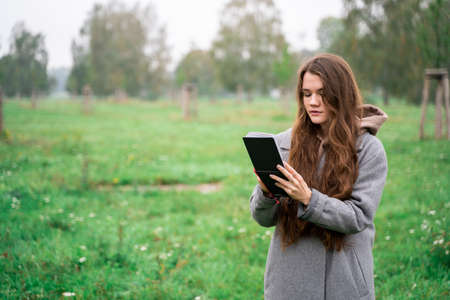 Young brunette woman dressed casually in warm coat holding paper notebook making notes or paints in green fresh park with wet grass on rainy early cloudy autumn day. Holiday, leisure, lifestyle, hobby