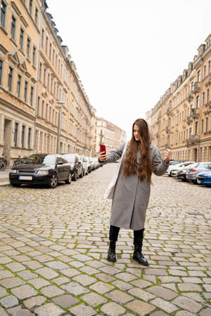 Young brunette woman dressed casually in grey coat walking on street road near residential buildings on rainy cloudy early autumn day making selfie pictures on smart phone. Holiday, leisure, lifestyle Zdjęcie Seryjne