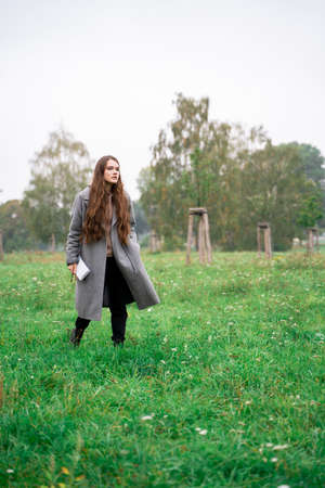 Portrait of young brunette woman dressed casually in warm coat holding paper notebook walking in green fresh park with wet grass on rainy early cloudy autumn day. Holiday, leisure, lifestyle, hobby