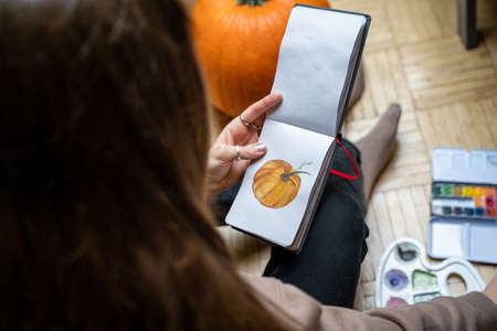 Young brunette long-haired woman sitting on floor drawing pumpkin with watercolor palettes and brushes in home bedroom near pumpkin on autumn weekend day. Hobby, arts, education and leisure activity